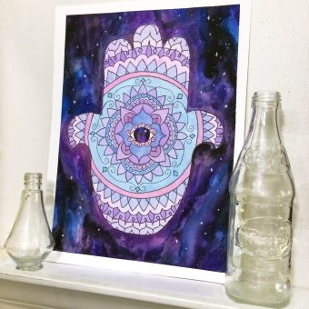 Watercolor mandala artwork of a hamsa mandala with a galaxy eye and background.
