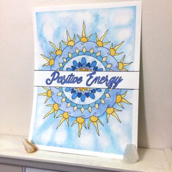 A watercolor mandala of the words 'Positive Energy' in script surrounded by a mandala filled with sky and sun-like patterns.